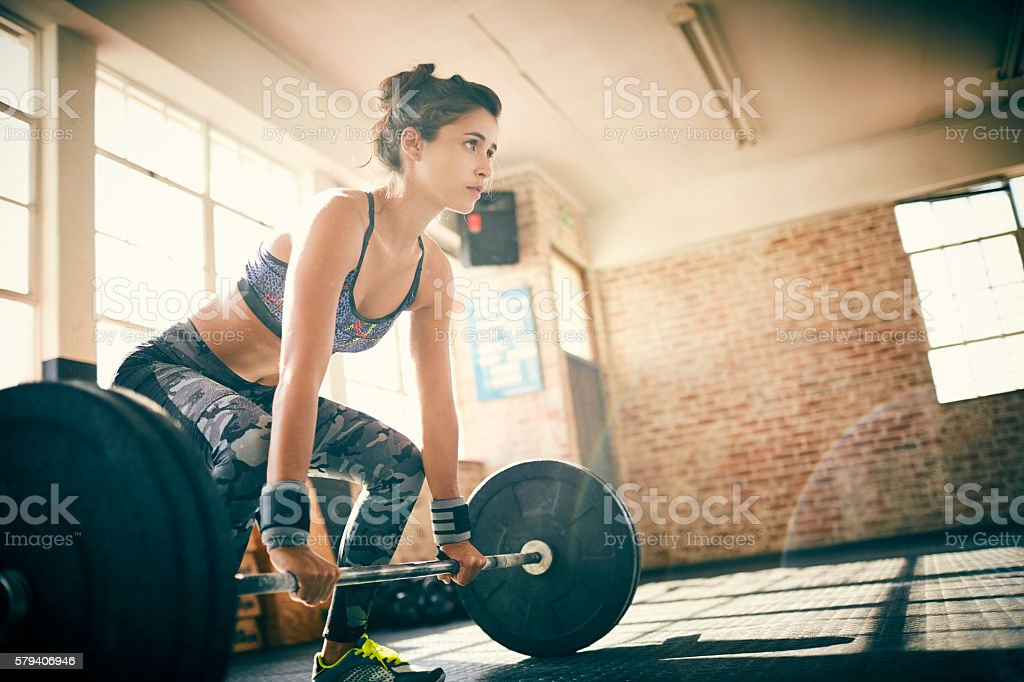 Low angle view of determined woman deadlifting with barbell stock photo