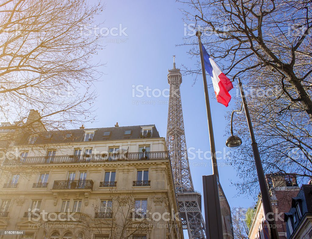 Low angle view of Eiffel tower between houses,trees stock photo