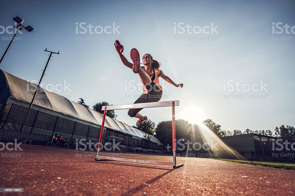Low angle view of female athlete hurdling on sports race. stock photo