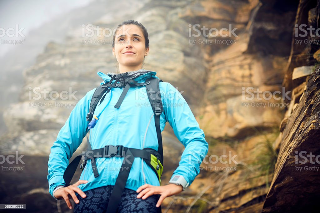 Low angle view of female hiker standing against rock formation stock photo