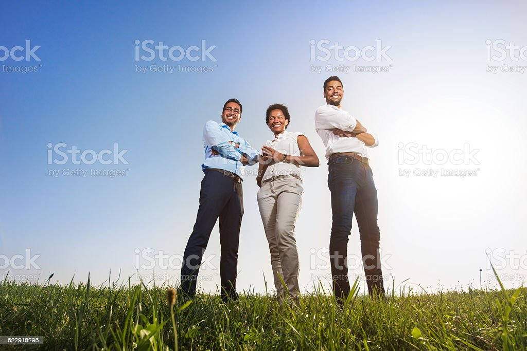 Low angle view of happy business colleagues with crossed arms. stock photo