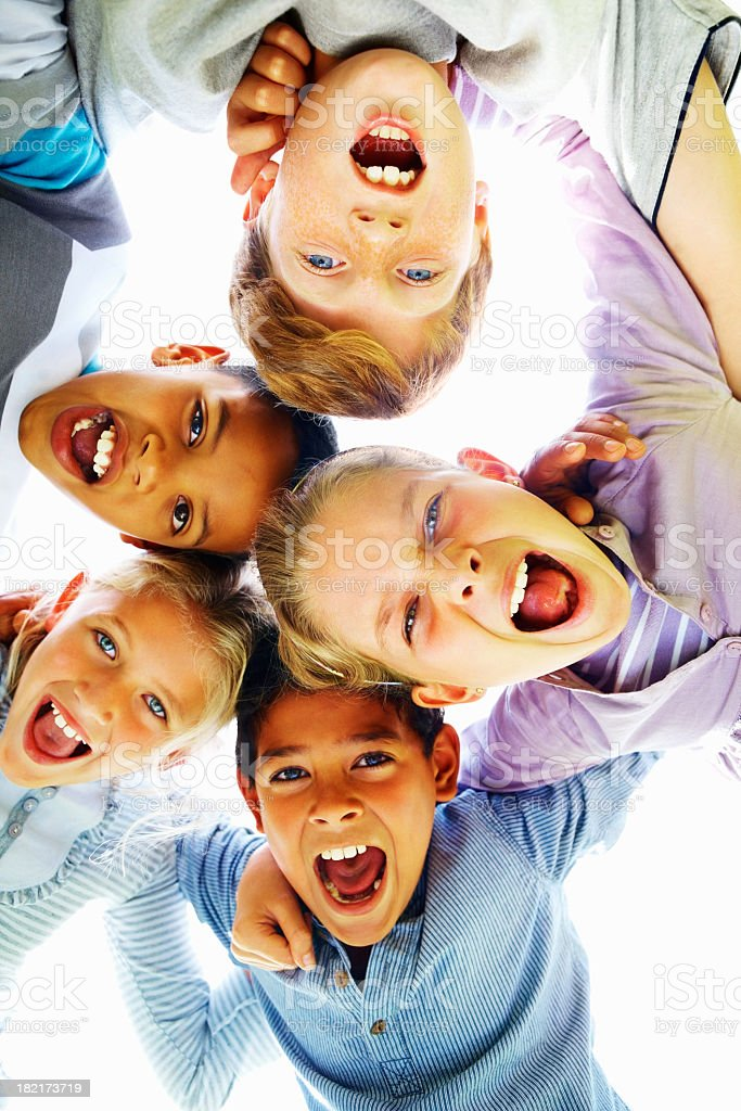 Low angle view of happy children huddling together royalty-free stock photo