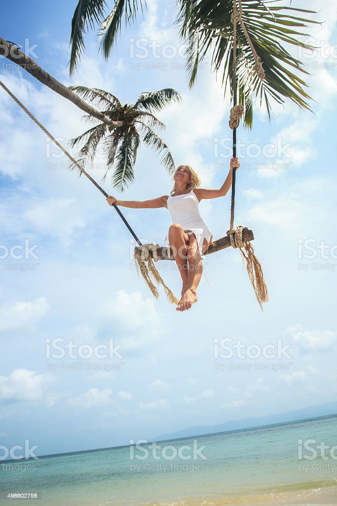 Low angle view of happy woman swinging on the beach. stock photo