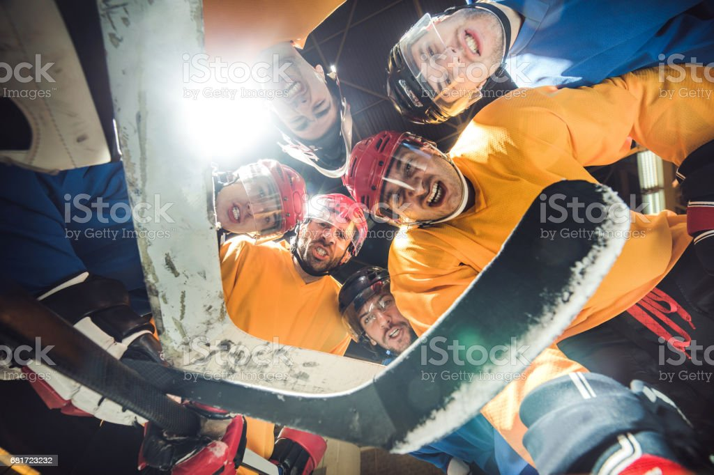Low angle view of ice hockey team making tough facial expressions. stock photo