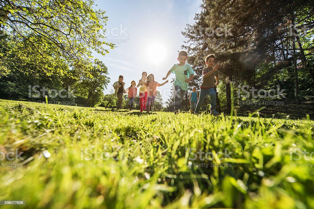 Low angle view of large group of children running outdoors. stock photo