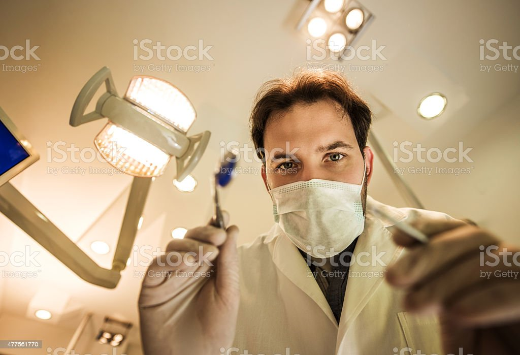 Low angle view of male dentist ready for dental examination. stock photo