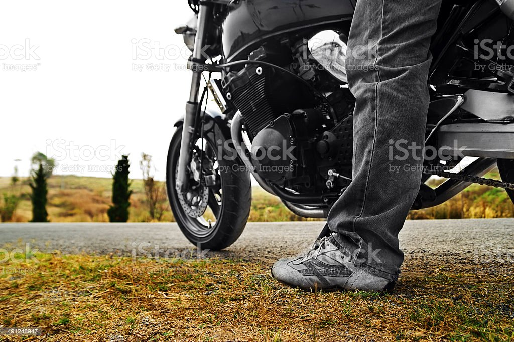 Low angle view of man riding bike against clear sky stock photo