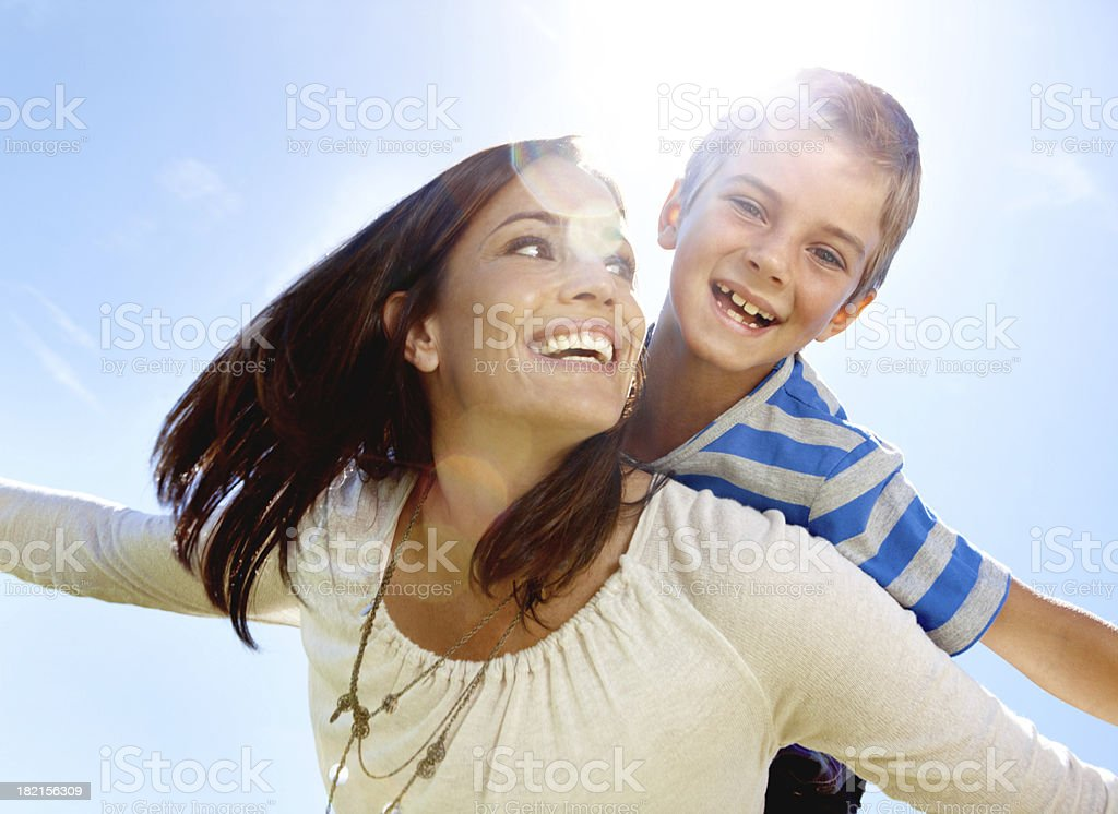 Low angle view of mom carrying son on back stock photo
