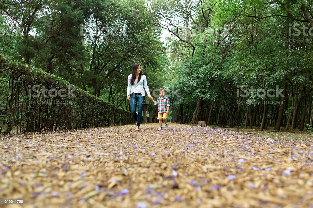 Low angle view of mother and son walking at park stock photo
