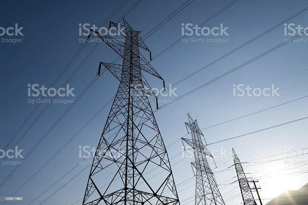 Low angle view of power lines against a sunny morning sky royalty-free stock photo