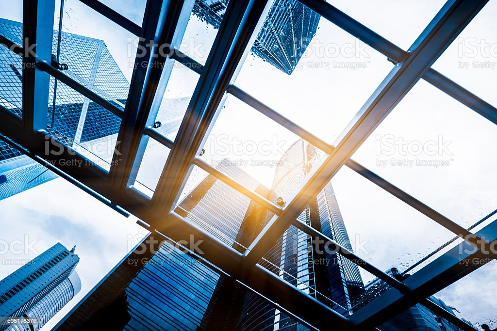low angle view of skyscrapers through glass canopy stock photo