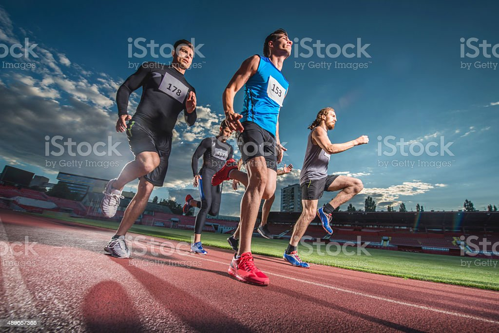 Low angle view of sports team jogging on a stadium. stock photo