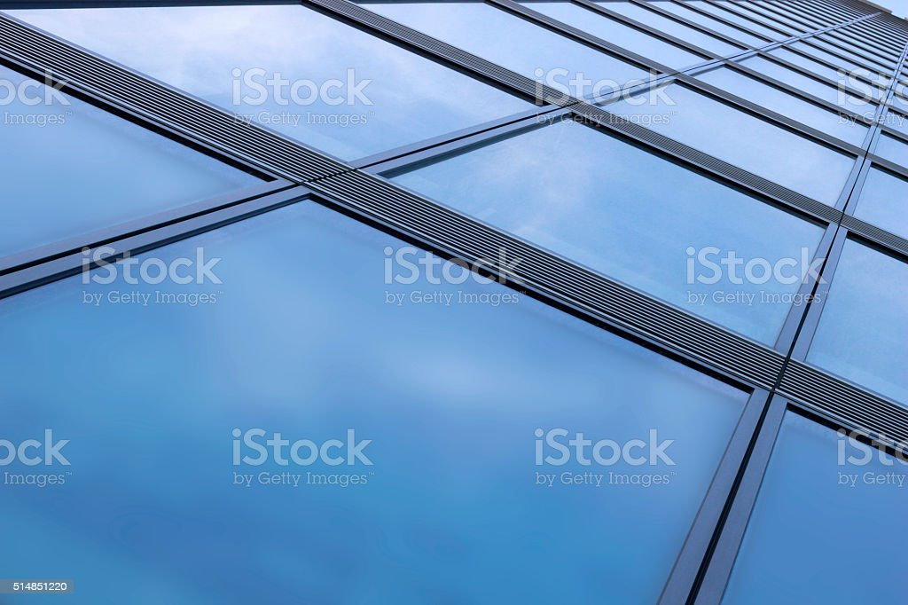 Low angle view of structural glass facade reflecting bright sky stock photo
