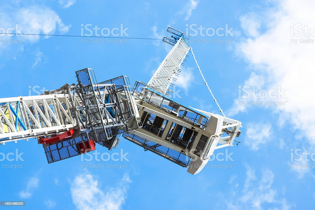 Low angle view of tower crane cabin against blue sky stock photo