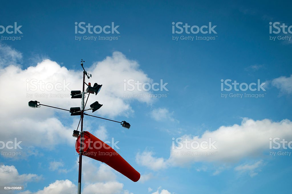 Low angle view of Windsock with street lamp against sky stock photo