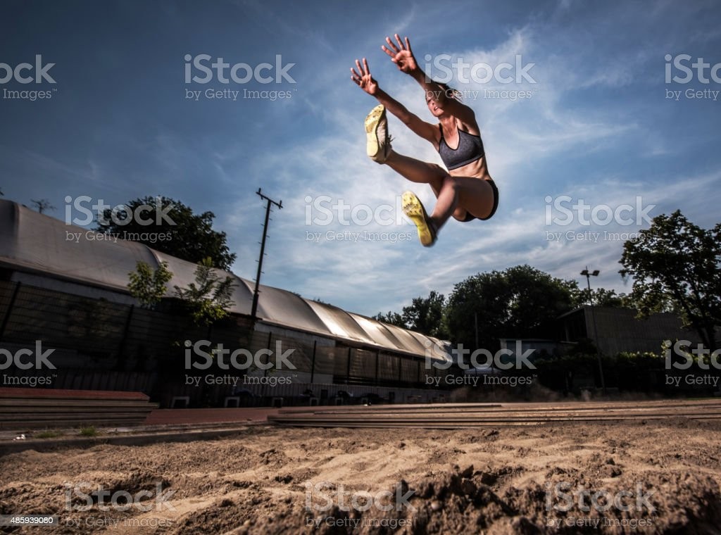 Low angle view of young athletic woman in long jump. stock photo