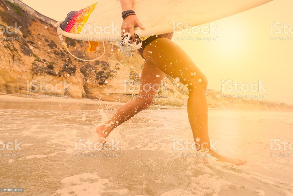Low Angle Women Surfer Running Into The Ocean At Sunset stock photo