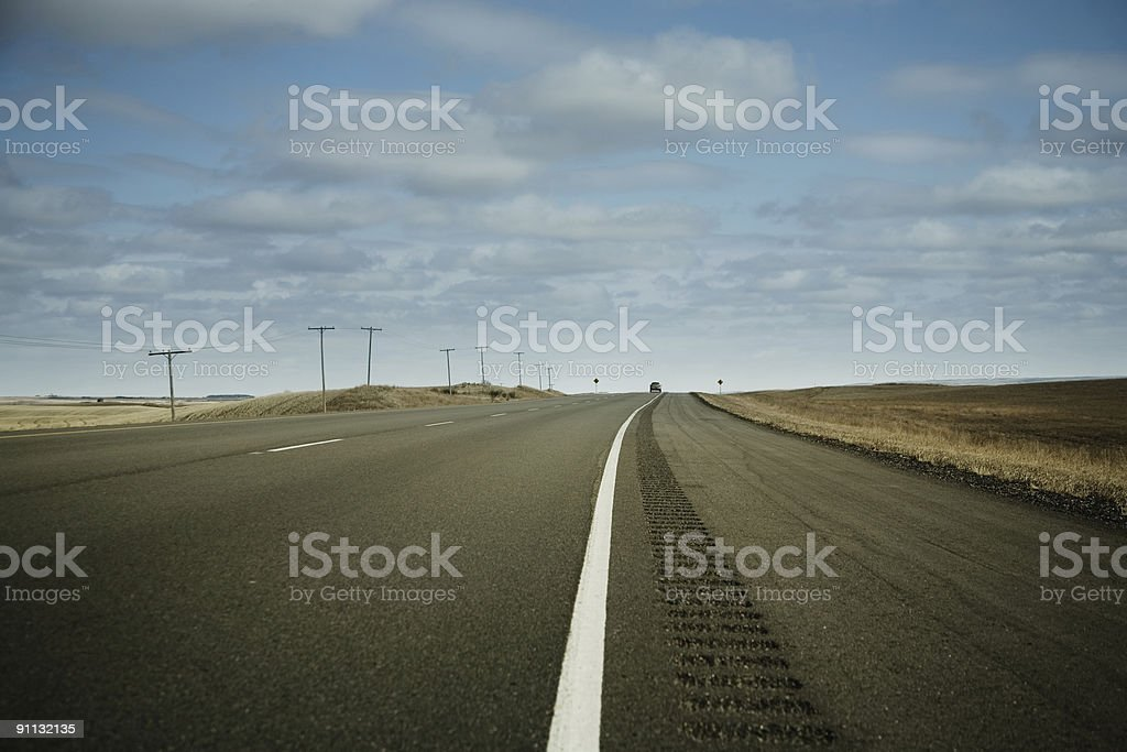 Low angled view of a bitumen road and a car in the horizon. royalty-free stock photo