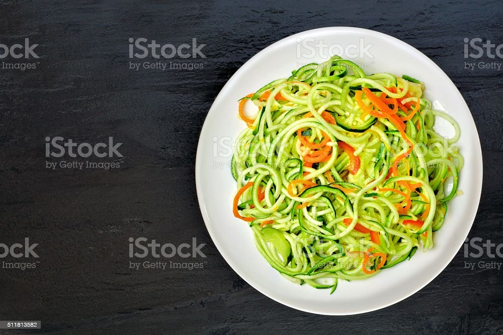 Low carb zucchini noodle dish on dark slate stock photo