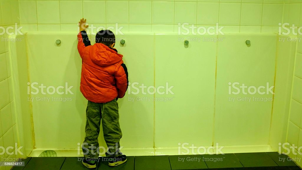 low child pees in a public urinal as adults stock photo
