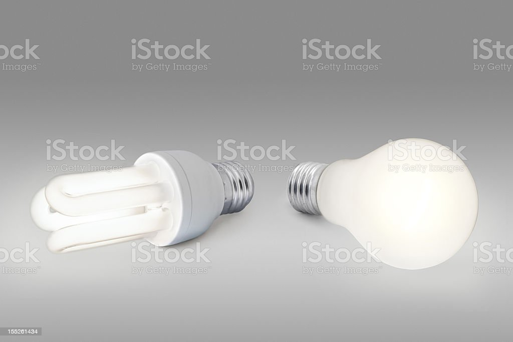 Low energy against normal light bulb stock photo