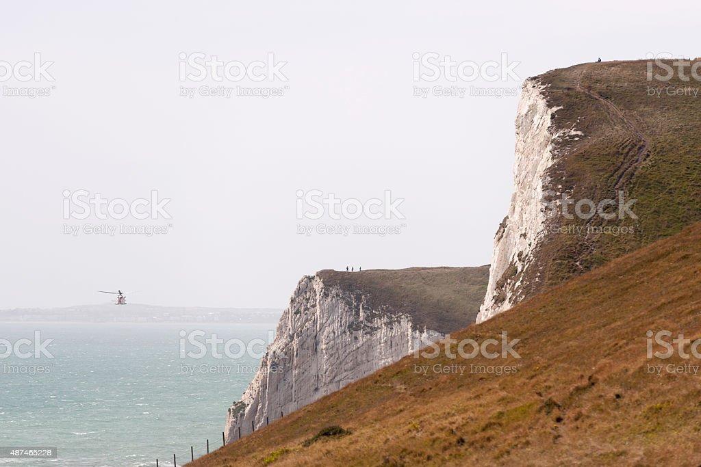 low flying uk coastguard helicopter near durdle door, dorset stock photo