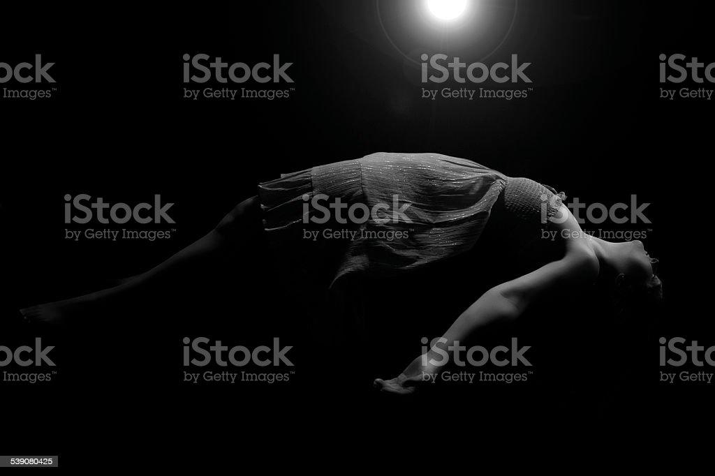 Low Key Female Levitating With Lens Flare stock photo