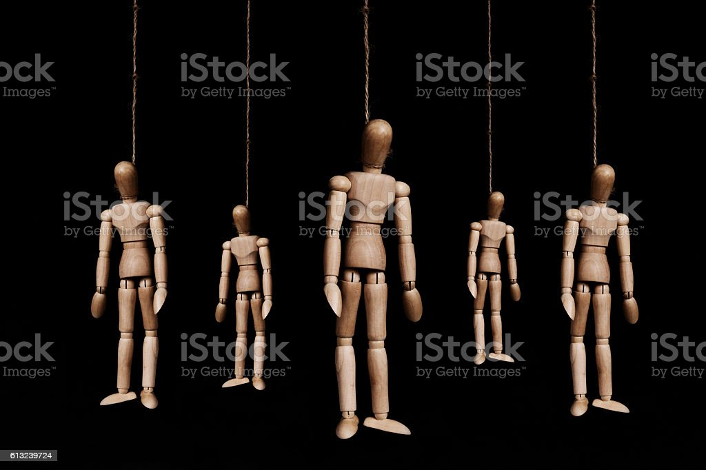 Low key, group of wooden figures hangman by rope stock photo