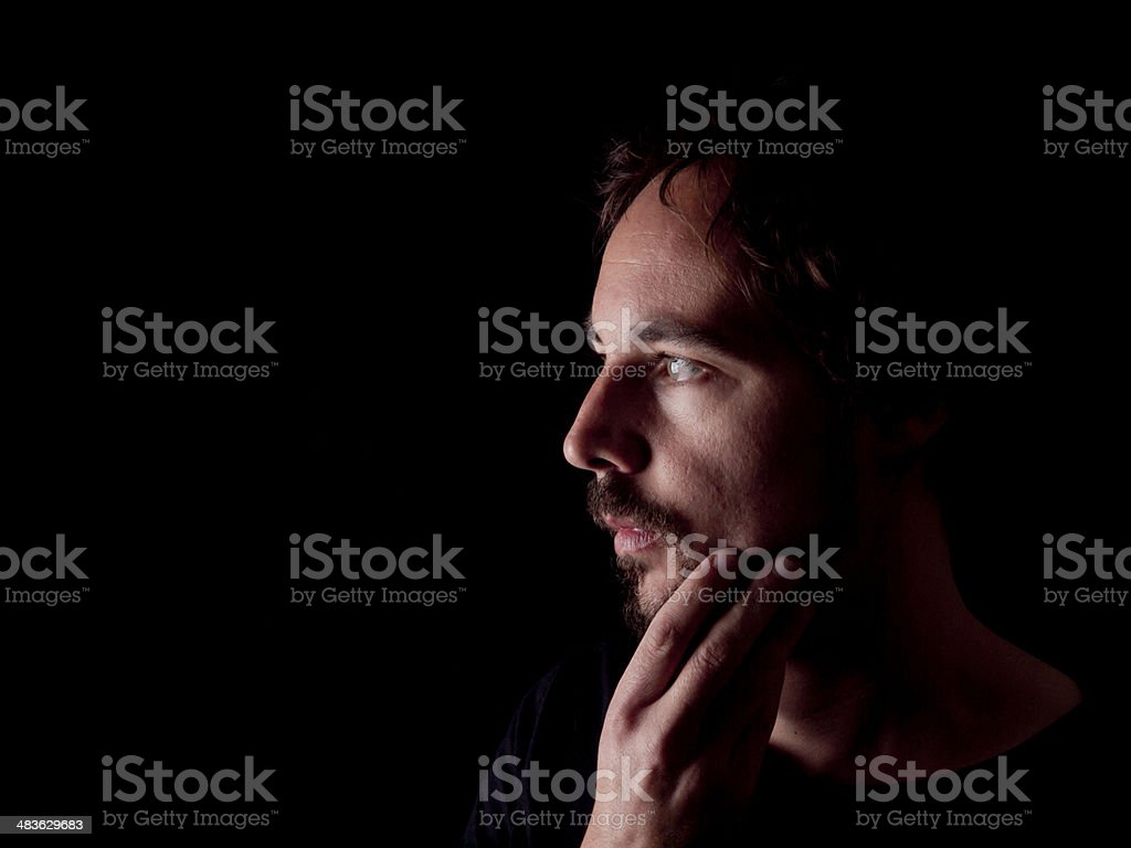Low key image of a pondering bearded man stock photo