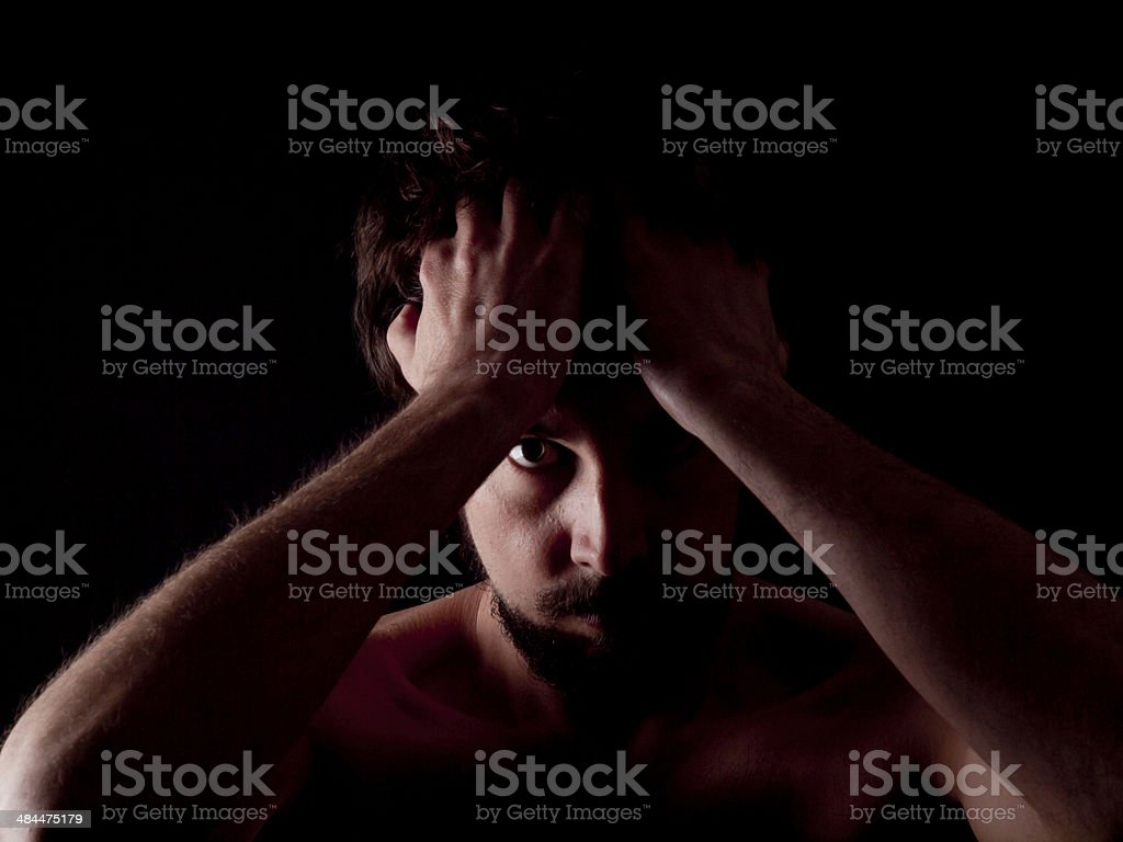 Low key image of an angry bearded man stock photo