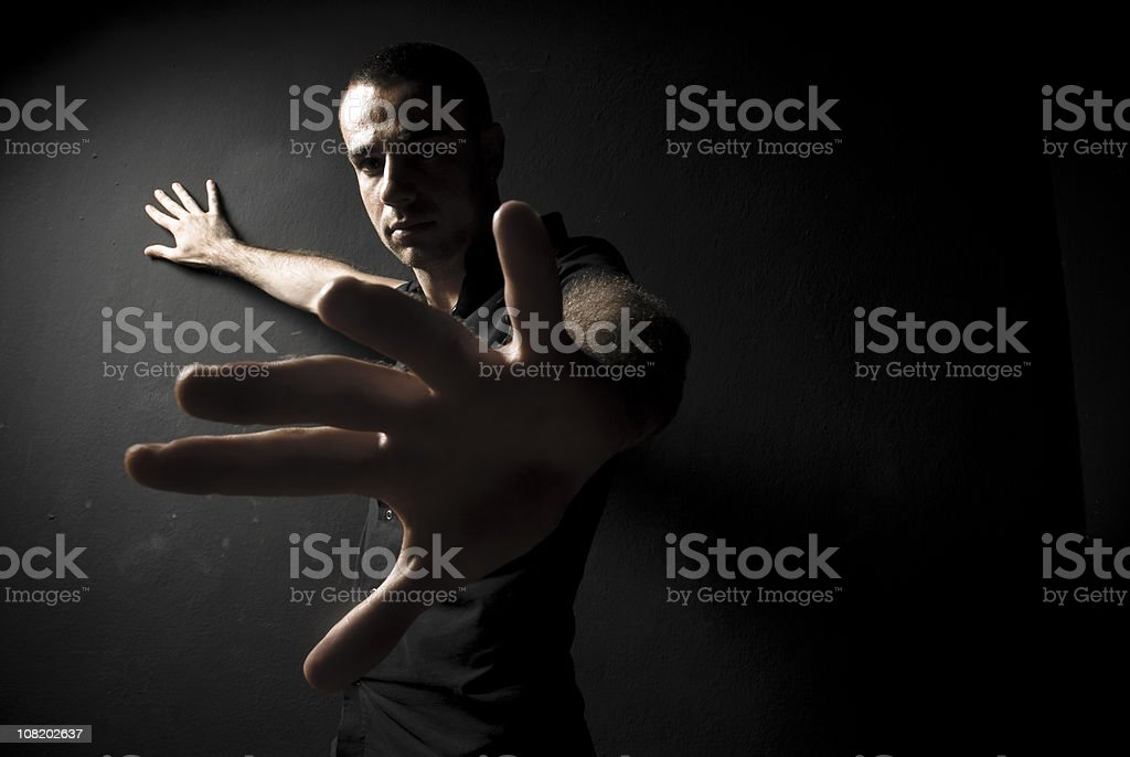 Low Key Image of Man Holding Hand  with Palm Outwards stock photo