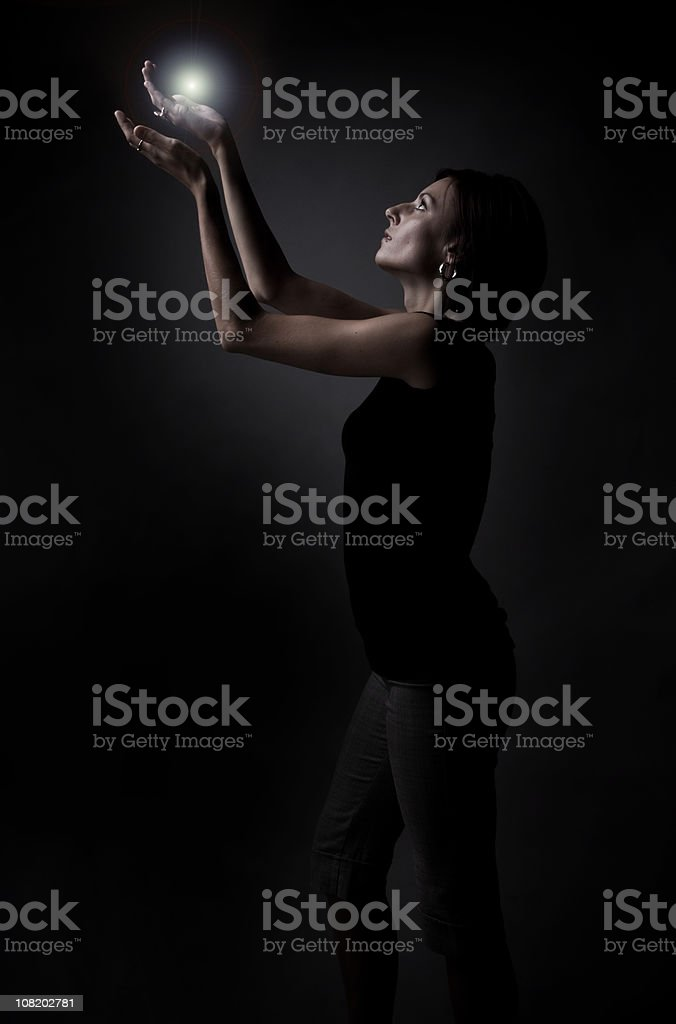 Low Key of Woman Holding Light in Hands royalty-free stock photo