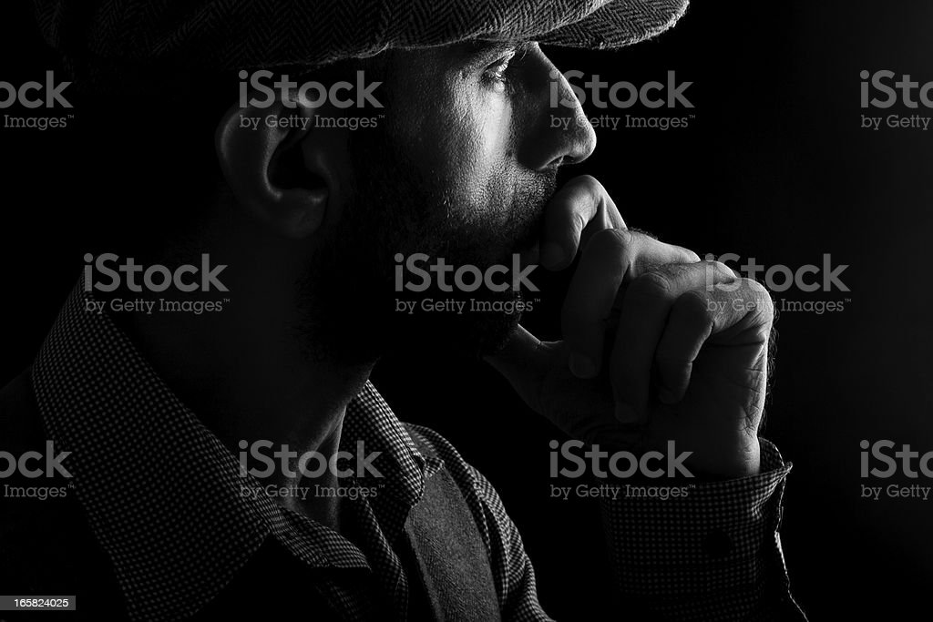 Low key portrait of man with hat thinking in dark stock photo
