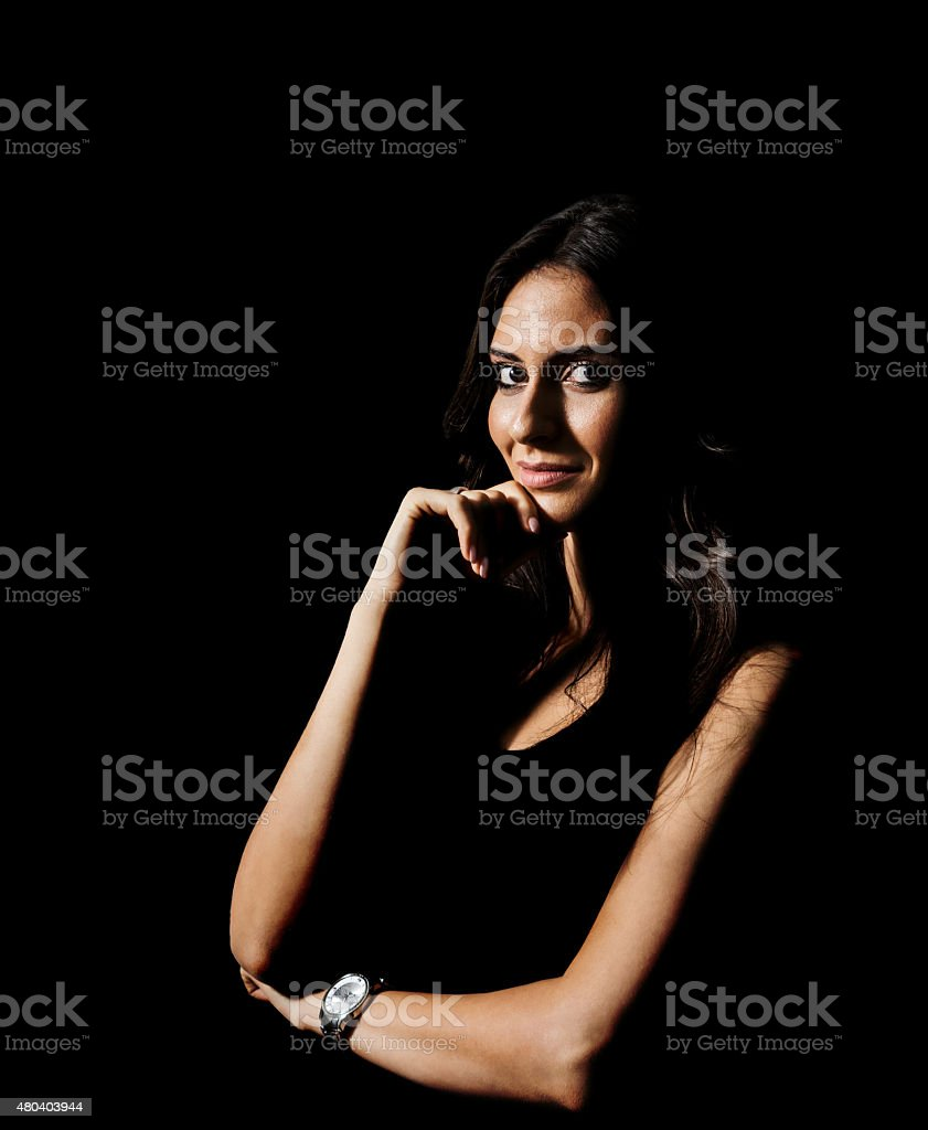 Low key portrait of young hispanic woman looking at camera stock photo