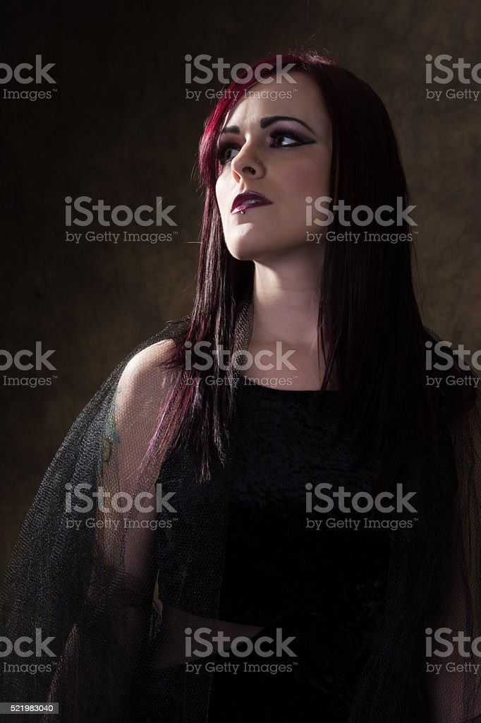 Low key waist up portrait of woman with side lighting. stock photo