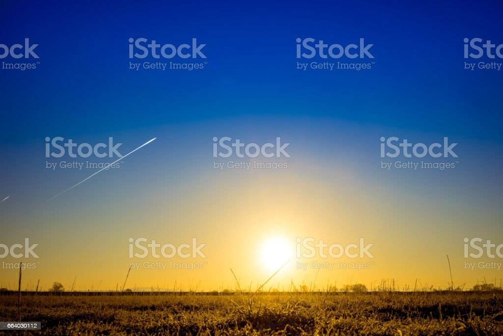 Low Level Sun Rise with Two Vapour Trails stock photo