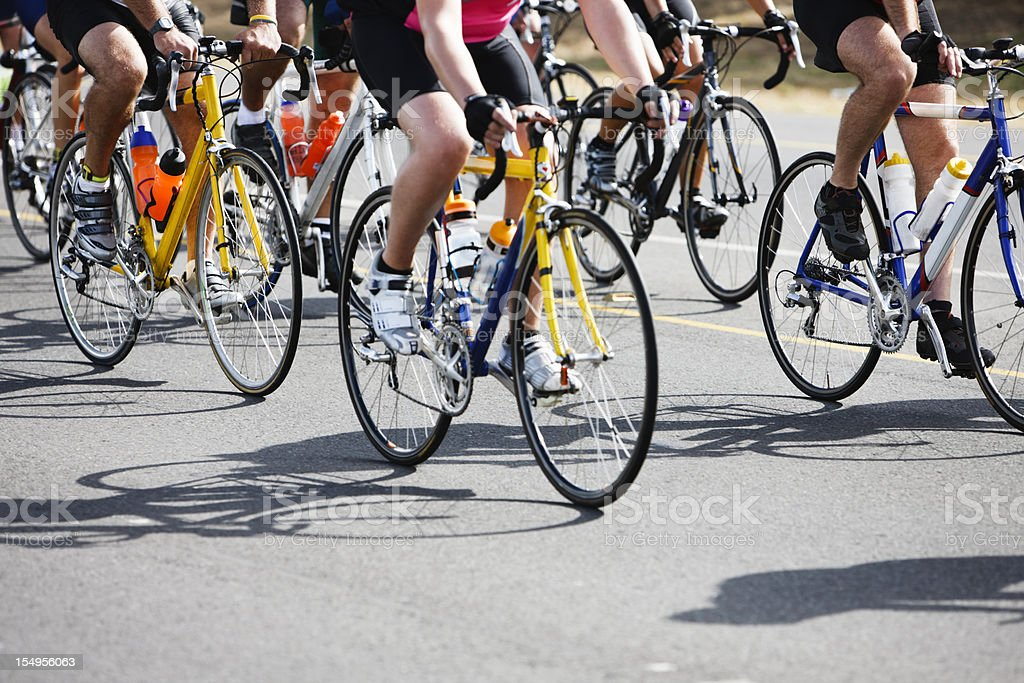 Low level view of racing cyclists and their shadows stock photo