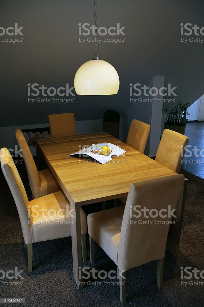 Low lit wooden dinner table stock photo