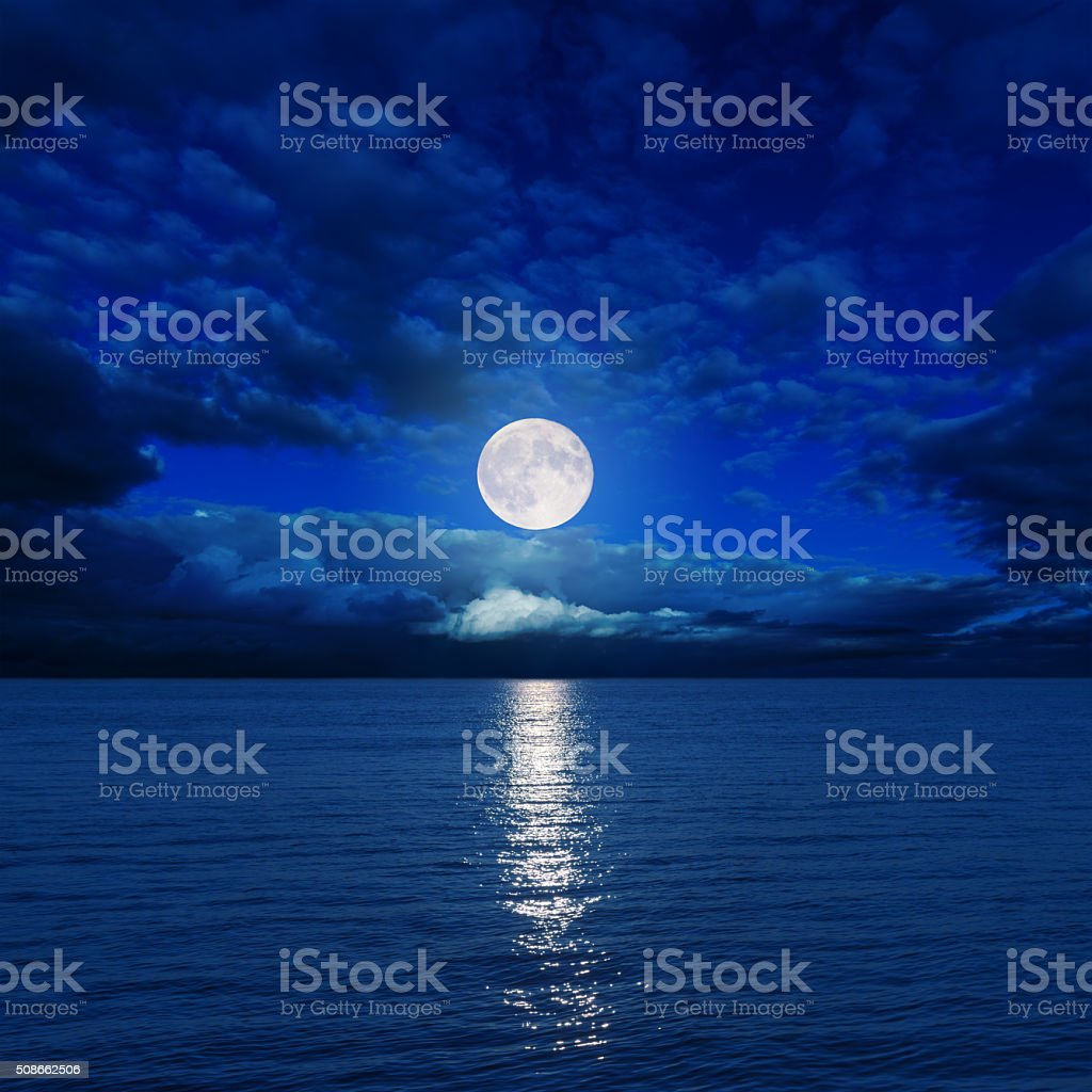 low moon in clouds over river stock photo