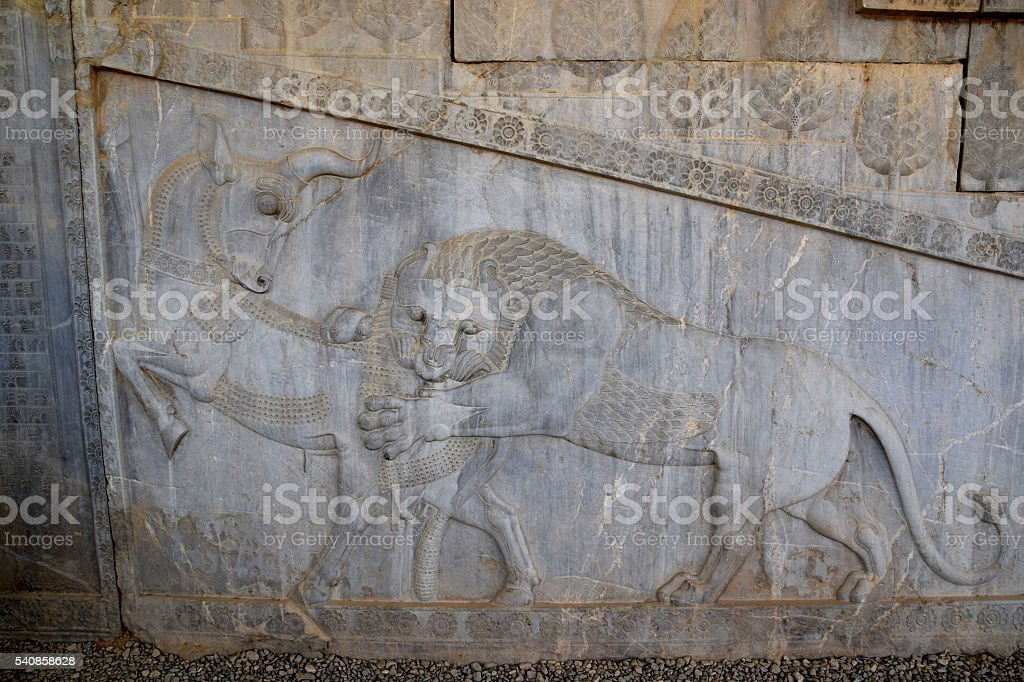 Low (bas) relief in Persepolis, Iran, lion attacking bull stock photo