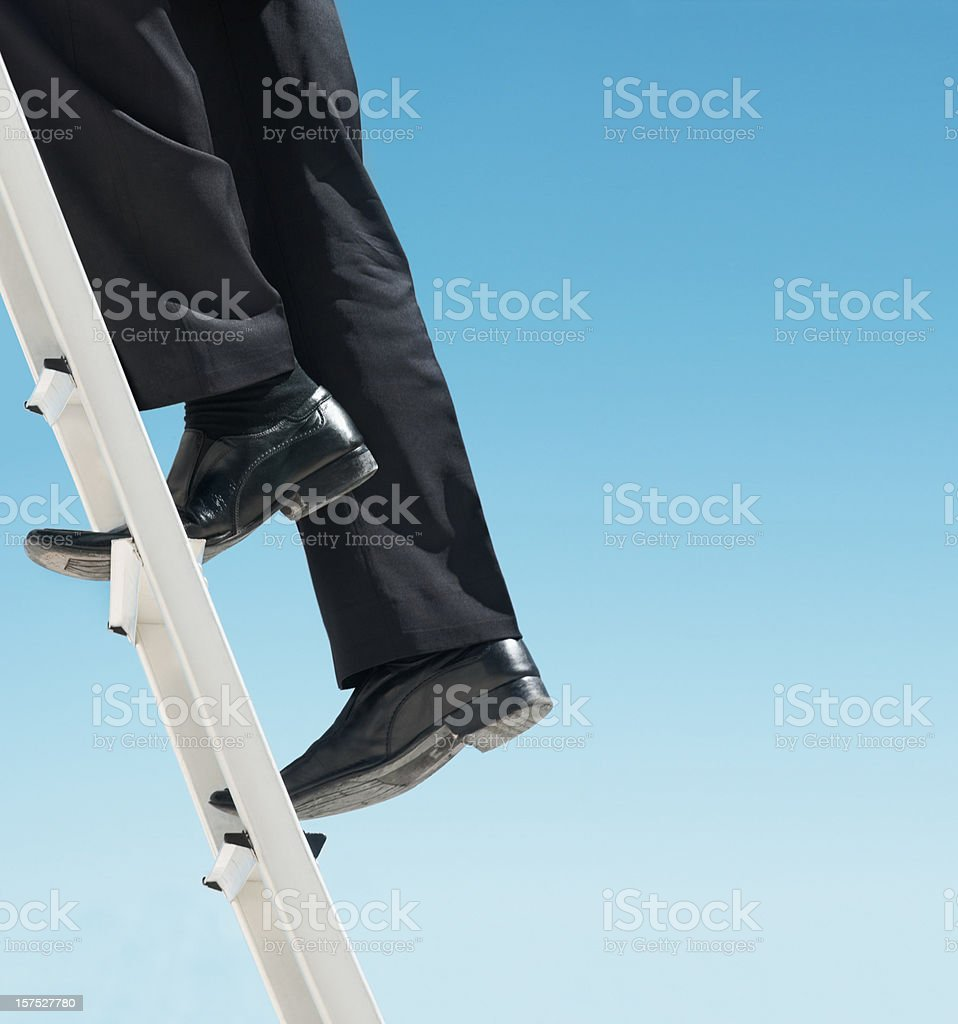 Low section of a business man climbing the ladder stock photo