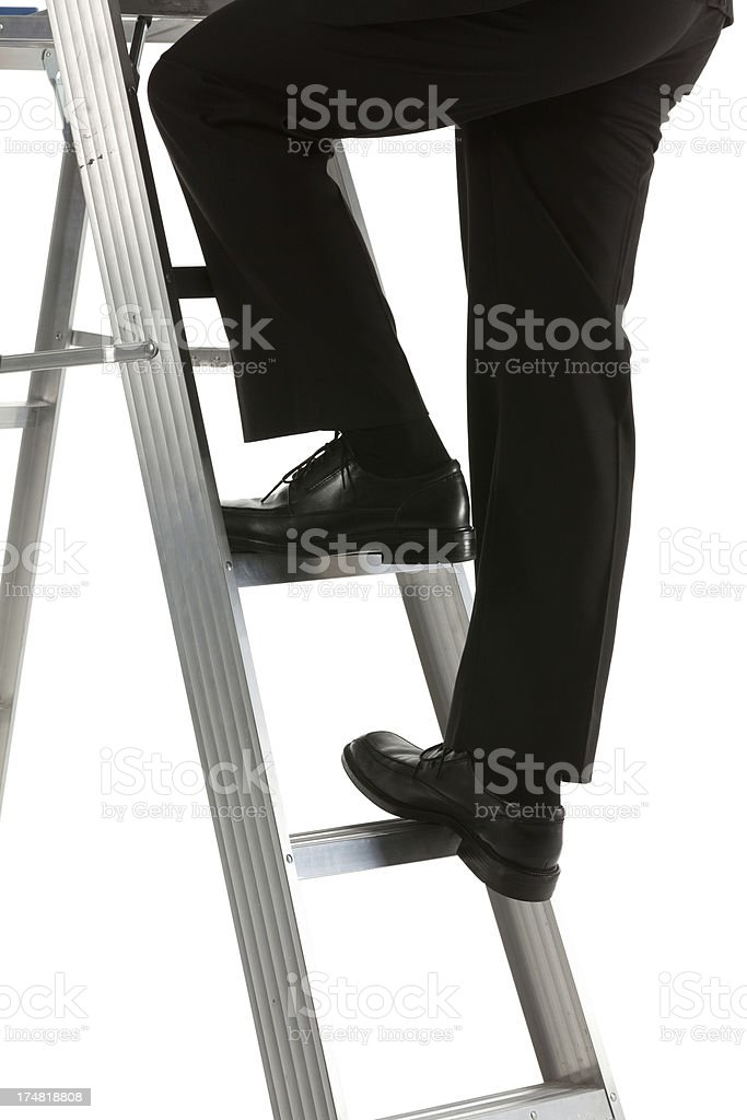 Low section of a businessman climbing the ladder royalty-free stock photo