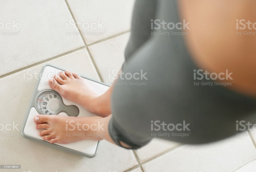 Low section of a dieting woman weighing herself stock photo