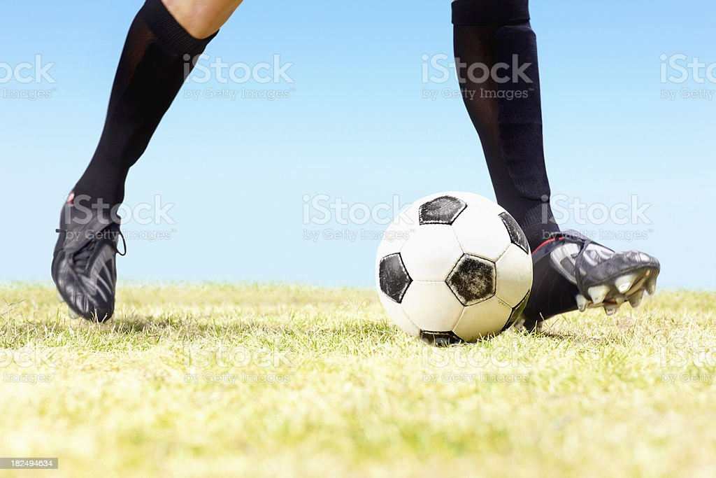 Low section of a footballer dribbling the ball royalty-free stock photo