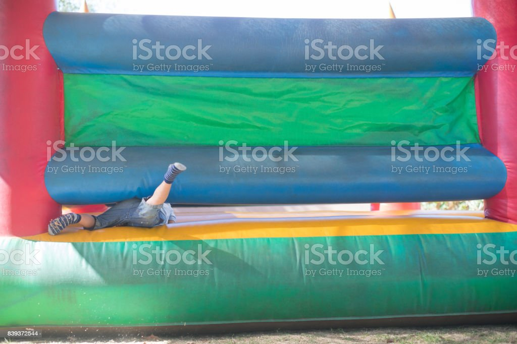 Low section of boy playing on bouncy castle stock photo