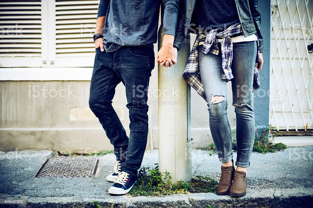 Low section of couple holding hands at pole stock photo