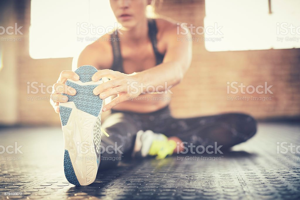 Low section of female doing stretching exercise in gym stock photo