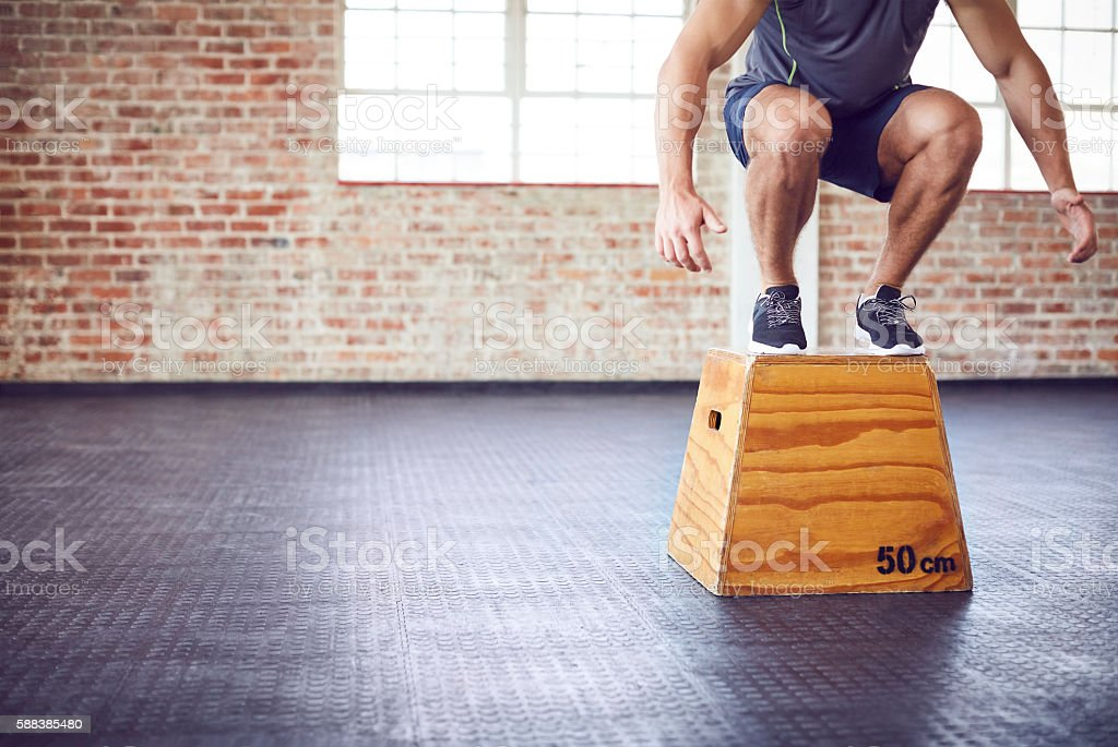 Low section of fit male athlete box jumping in gym stock photo