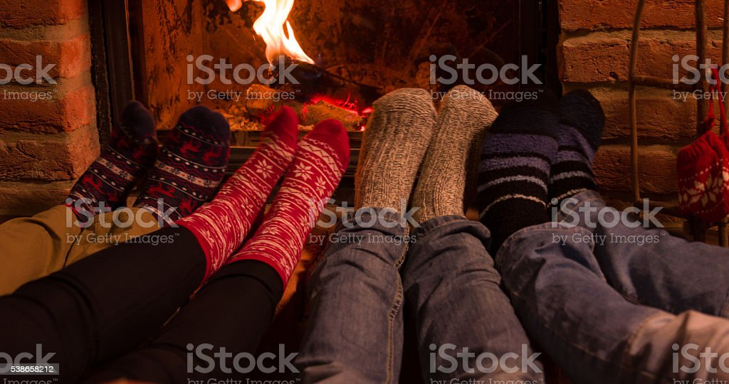 Low section of friends resting legs at fireplace stock photo