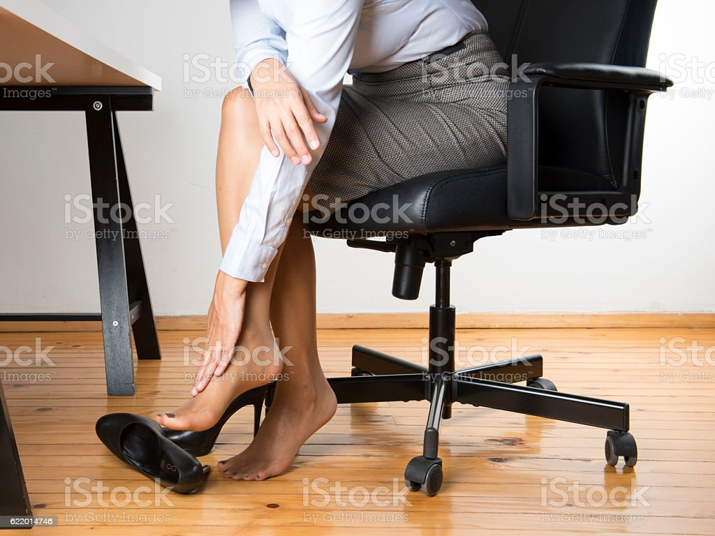 Low Section of Office Worker Massaging Foot stock photo